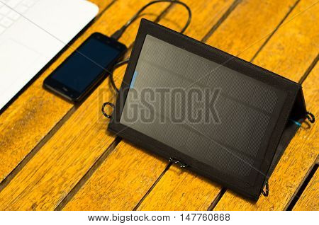 Portable solar charger sitting on wooden surface next to laptop computer and mobile phone, as seen from above, modern technology concept.