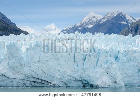 Margerie Glacier in Glacier Bay National Park and Preserve in Southeast Alaska is twenty-one miles long and one mile wide with layers of rock debris mixed with ice.