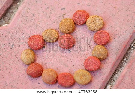 Closeup fresh red and brown colored crunchy dog food lying on stone tiles surface, shaped in heart formation.