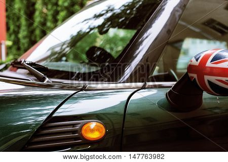 vintage car detail, concept of British Patriotism shown as flag on mirror, trees in reflection windshield, body part close up reflection