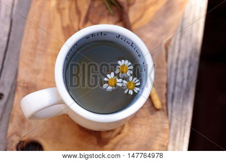 Chamomile tea with chamomile daisy flowers in a hot white cup on a wooden rustic cutting board and a spoon. This home remedy is known to help sleep and aid a sore throat