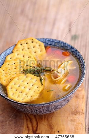 Chicken noodle soup in a blue and white bowl with crackers, all sitting on a wood cutting board.