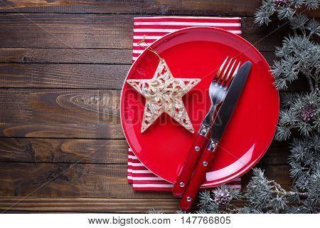 Empty late knife and fork napkin and christmas decorations in white and red colors on dark wooden table. Christmas table setting.Top view. Place for text. Selective focus.