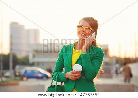 Young attractive woman talking on smartphone. Businesswoman holding a cup of coffee and fashionable bag. A successful and positive. Soft focus.