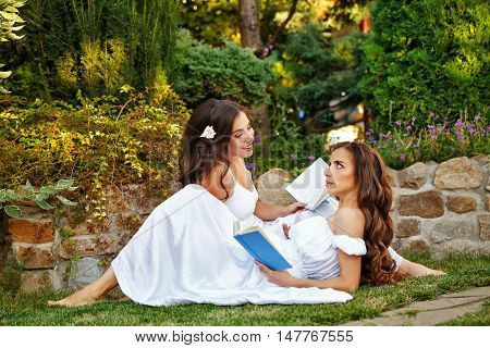 Two cute sisters reading a book while sitting lawn. Girls discuss the reading. Literary discussion. Poetry readings. They are in long white dresses.