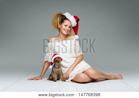 Beautiful girl in lace dress and red santa cap sitting with pretty yourkshire terrier in christmas hat. Studio shot over grey background. Copy space.