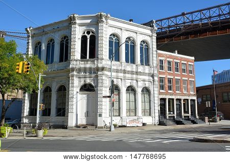 New York, United States of America - September 24, 2015. Building on the intersection of Old Fulton St and Front St in Brooklyn, New York , with Brooklyn Bridge, surrounding buildings and cars.
