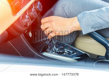Business man driver hand shifting the gear stick