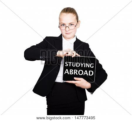 school girl in a business suit holds a pc tablet in his hands with inscription - studying abroad.