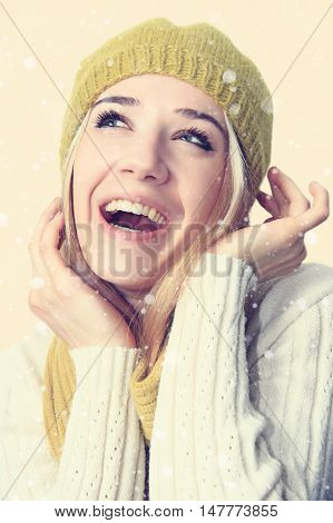 Young cheerful girl in a green beret and knitted scarf on a light background.