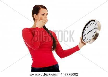 Young yawning woman holding a clock