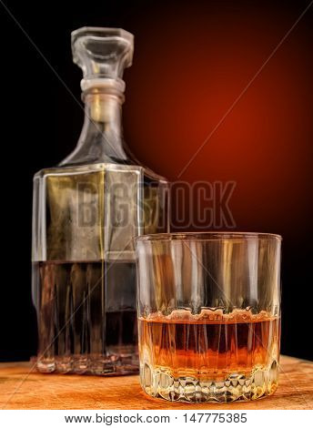 Glass with alcohol against the background of a decanter and a background with a gradient. Vertical format. Indoors. Color. Photo.