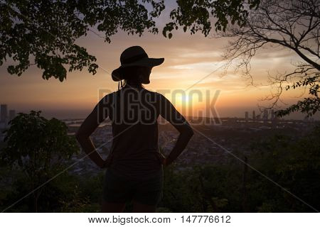 Silhouette of a young woman watching the sunset over Cartagena de Indias