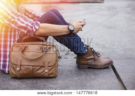 Young entrepreneur with boots and a casual attitude browsing on his smartphone in Brooklyn, New York