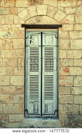 The old window with blue closed shutters in mediterranean stone house.