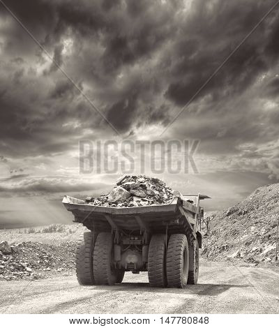 Heavy dump truck carrying the iron ore on the opencast mining on sunset - black and white image