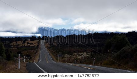 Country road at the alps in New Zealand South Island. Mountains of Fiordland National Park in the background.