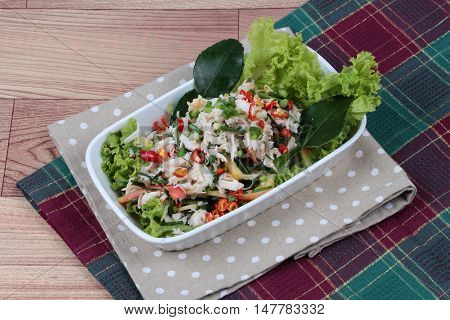Spicy and sour mixed herb salad with crab   on red green. Side view.