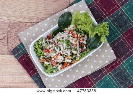 Spicy and sour mixed herb salad with crab   on red green. Top  view.