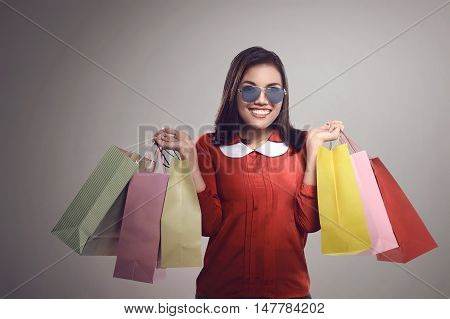 Happy Glad Asian Woman In Glasses Holding Paper Bags