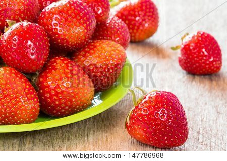 Close-up view of plate with fresh strawberry on wooden floor
