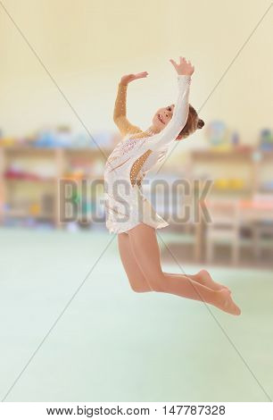 Beautiful little girl gymnast dressed in sports swimsuit, jumps high.On the background of the room where children live, and are on the shelves of toys.