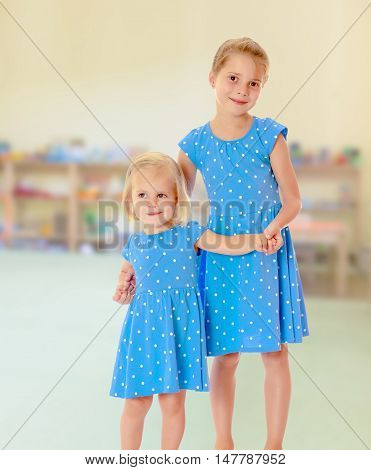 Against the background of a child's room .Two charming little girls, sisters , in identical blue dresses with polka dots , cuddling.