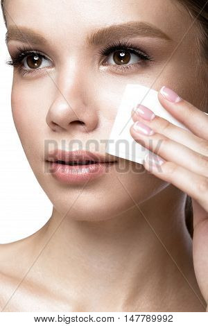 Beautiful young girl with wipes for removing makeup and French manicure. Beauty face. Picture taken in the studio on a white background.