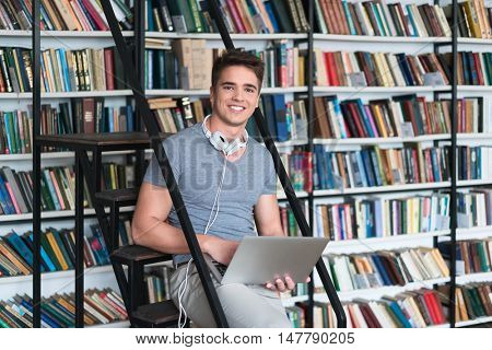 Smiling man with laptop in library