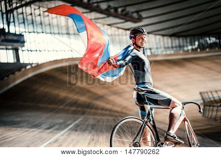 Bicyclist with flag on a sports track