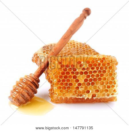 Honey dipper with honeycomb close up on white