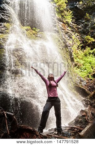 Young woman standing in front of waterfall with her hands outstretched. Caucasian female tourist in forest with her arms wide open. Happy tourist woman looking at the waterfall. Lifestyle adventure vacations concept.