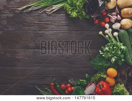 Border of fresh organic vegetables and greens on wood background. Healthy natural food on rustic wooden table with copy space. Italian cuisine cooking ingredients top view, soft toning