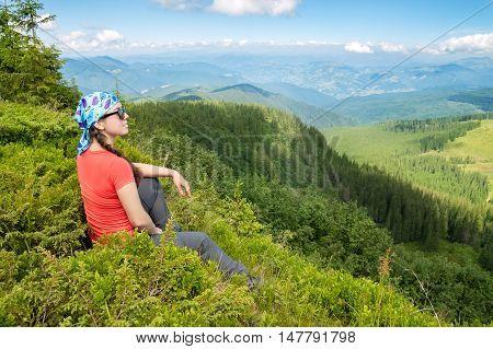 happy woman tourist admiring views of the mountains. Hiker girl enjoying beautiful mountain view. Tourist in the mountains. Hiking.