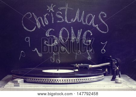retro old turntable with a plate on the background of the inscription in chalk on a blackboard / old Christmas song