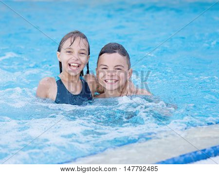 Smiling beautiful children in the swimming pool at aquapark. Happy teen boy and girl - brother and sister having fun together enjoyable time on vacation.