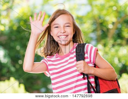 Smiling girl 10-11 year old stretching her hand up for greeting .Beautiful schoolgirl with backpack posing outdoors. Young student beginning of class after vacation.