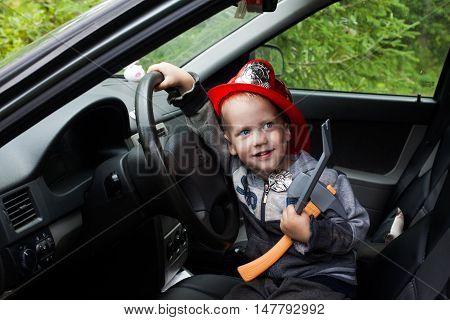 baby boy firefighter fireman suit, smiling, car, wheel, driver helmet uniform