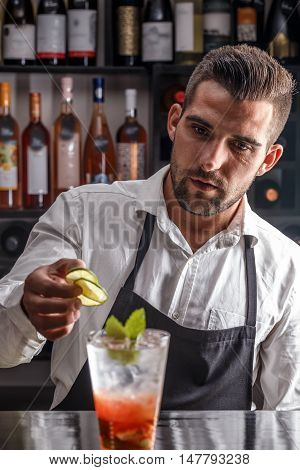 Barman decorating cocktail with lime in pub