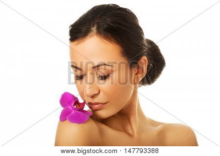 Woman with purple orchid petal on shoulder