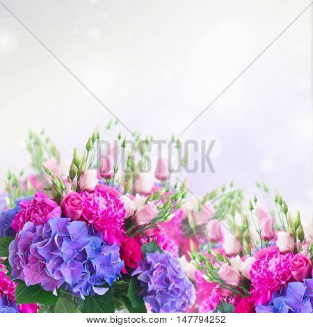 Bright pink peony, eustoma and blue hortensia flowers bouquet border with copy space on gray bokeh background