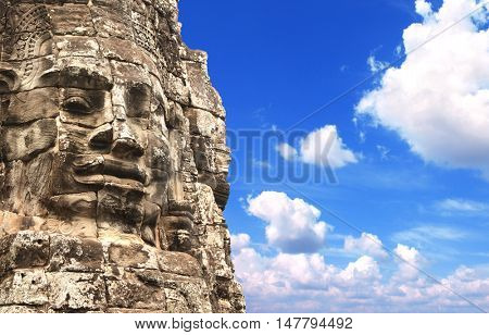 Giant stone face in Prasat Bayon Temple, famous landmark Angkor Wat complex, khmer culture, Siem Reap, Cambodia. On blue sky background