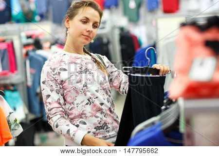 Woman choosing pants during shopping at garments apparel clothing shop