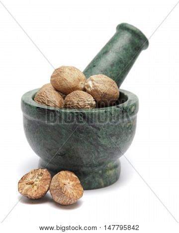Organic Nutmeg Seed or Jaiphal (Myristica fragrans) on marble pestle and over white background.