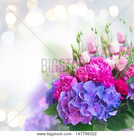 Bright pink peony, eustoma and blue hortensia flowers bouquet close up on gray bokeh background