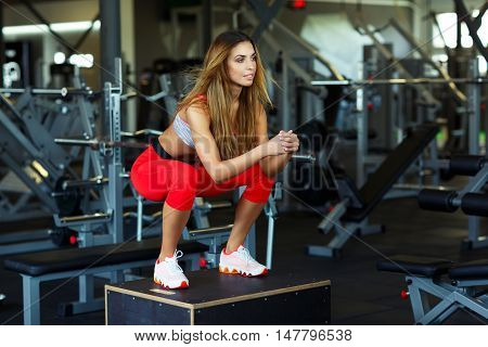 Fit young woman box jumping at a crossfit style. Female athlete is performing box jumps at gym