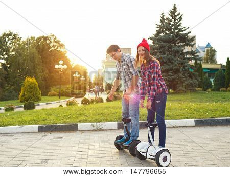 A young couple riding hoverboard - electrical scooter personal eco transport gyro scooter smart balance wheel. New modern technologies
