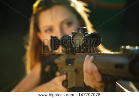A young girl with a gun for trap shooting aiming at a target