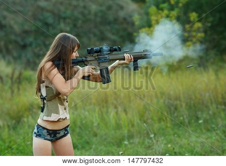 A young girl with a gun shooting at a target outdoors