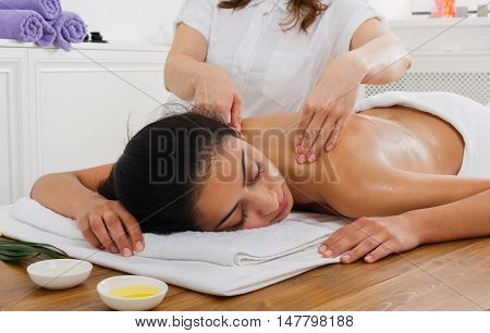 Female beautician doctor with woman patient in spa wellness center. Professional massagist make body back and shoulders massage to beautiful indian girl in health club or beauty parlor.